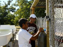 Image of ...Mahesh Boddu (left) and Ranjith Rajasegaram (right) attaching the CO2 tank to the Algal Raceway